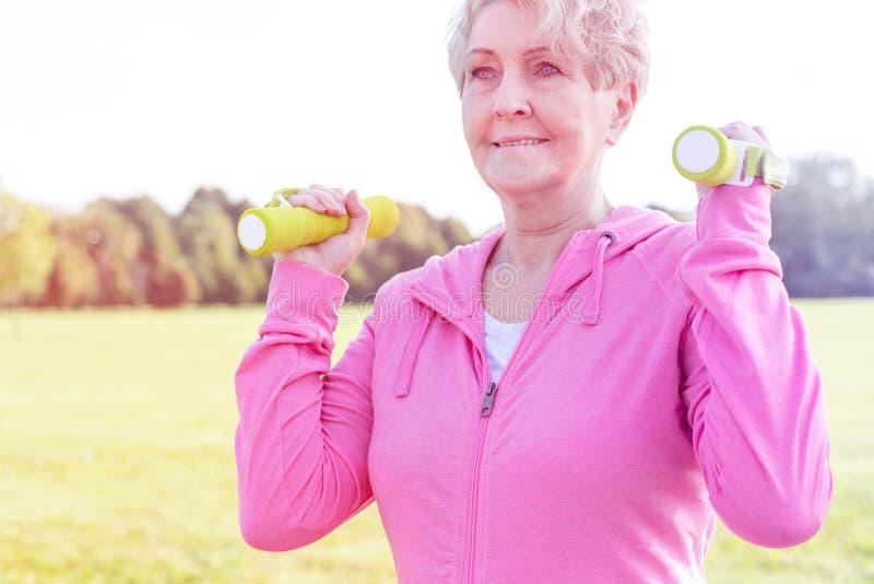 Ältere Frau mit Dummköpfen trainierend im Park stockfotografie