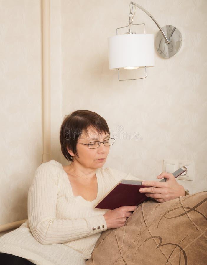 Ältere Frau mit einem Buch stockfotografie