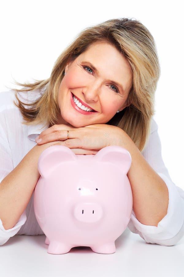 Ältere Frau mit einem Sparschwein. stockbilder