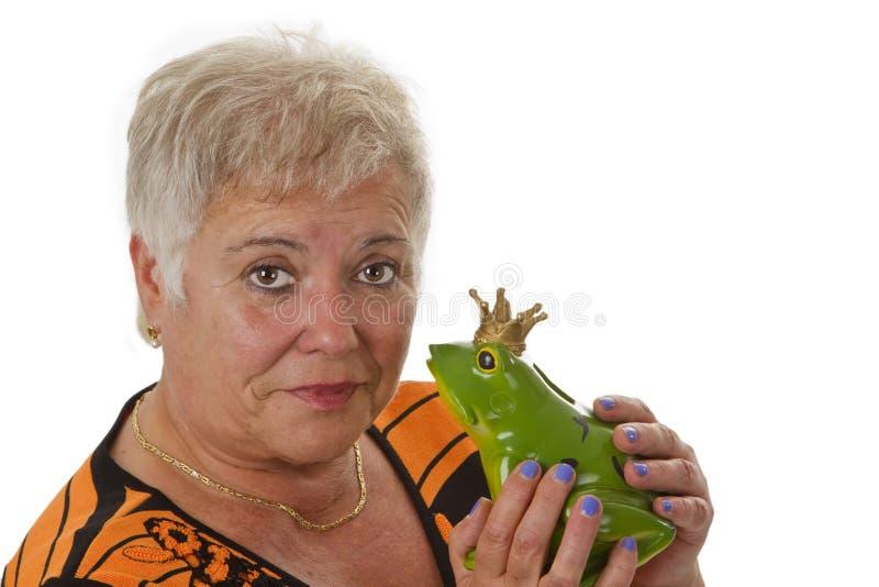 Ältere Frau mit einem Spielzeugfroschprinzen stockfotografie