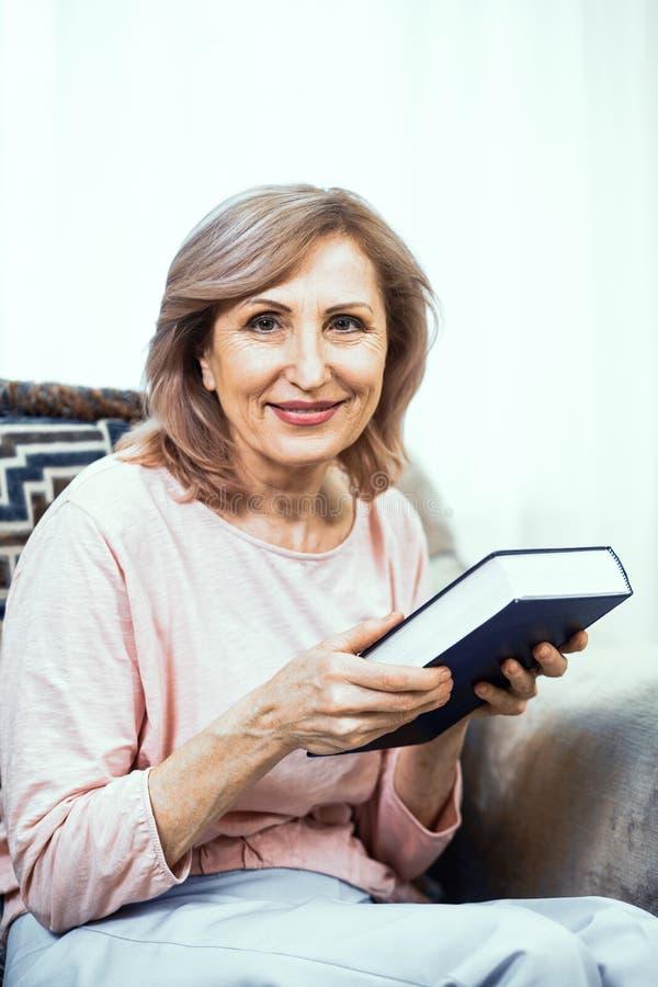 Ältere Frau mit einem starken blauen Buch in ihren Händen stockfotografie