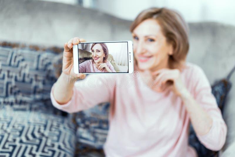 Ältere Frau mit einem Telefon in ihren Händen in der guten Laune steht zu Hause im Wohnzimmer still stockfotografie