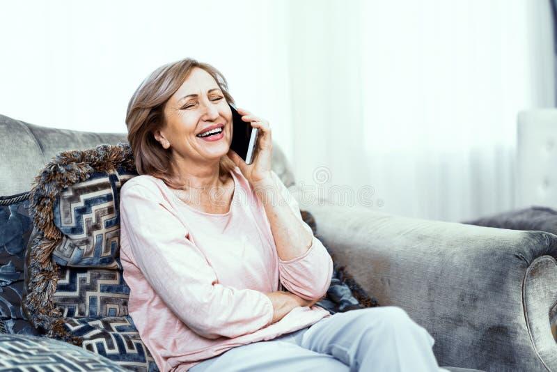 Ältere Frau mit einem Telefon in ihren Händen in der guten Laune steht zu Hause im Wohnzimmer still lizenzfreie stockfotos