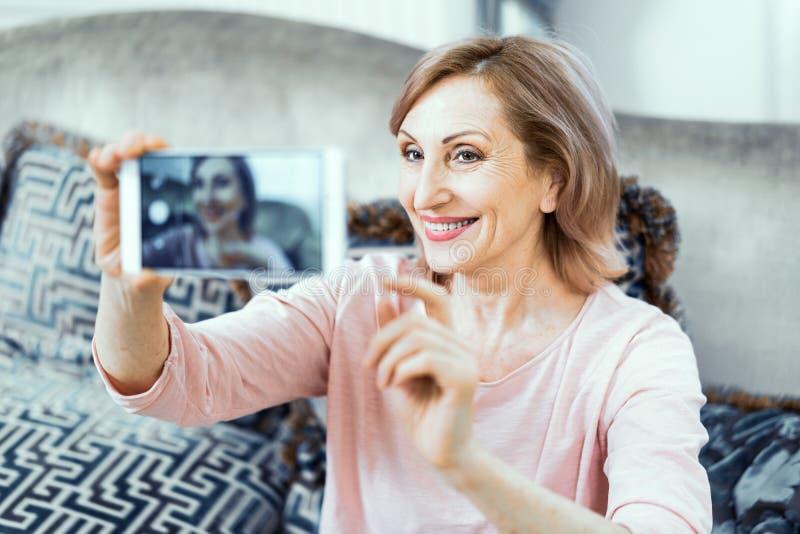 Ältere Frau mit einem Telefon in ihren Händen in der guten Laune steht zu Hause im Wohnzimmer still stockbild
