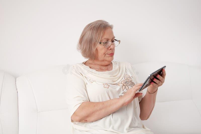 Ältere Frau mit einer digitalen Tablette lizenzfreies stockbild