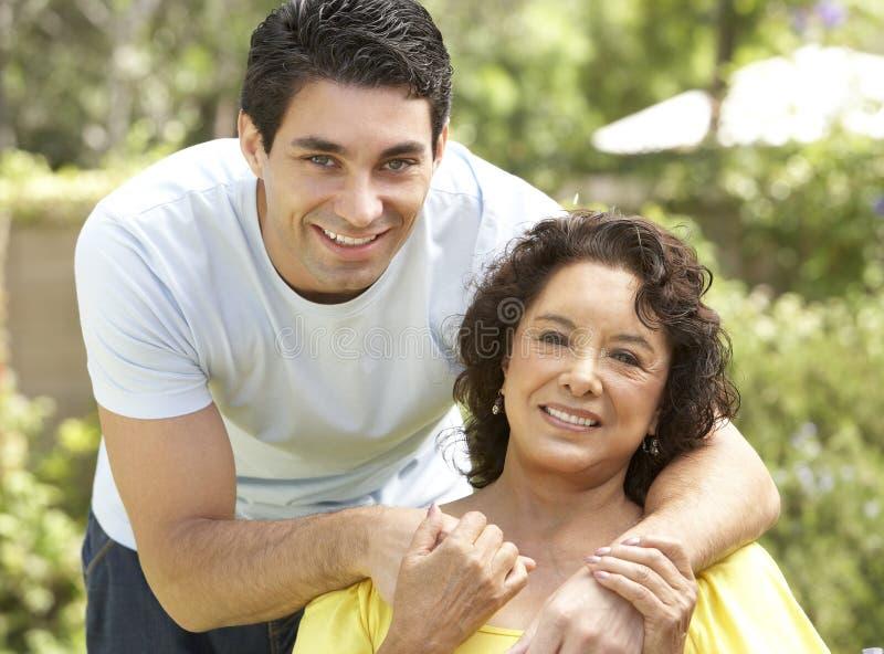 Ältere Frau mit erwachsenem Sohn im Garten stockfoto