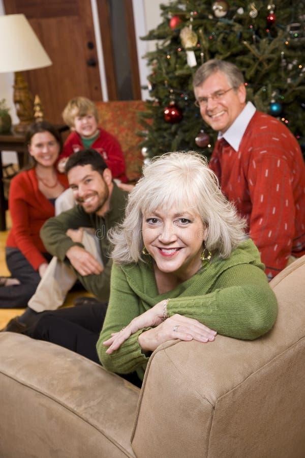 Ältere Frau mit Familie durch Weihnachtsbaum stockfotografie