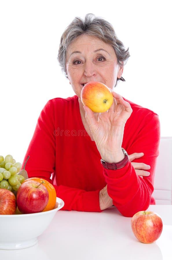 Ältere Frau mit Früchten - ältere Frau lokalisiert auf weißem backgro lizenzfreie stockfotos