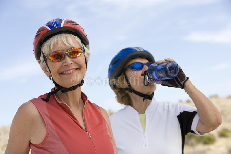 Ältere Frau mit Freund-Trinkwasser im Hintergrund lizenzfreie stockfotos
