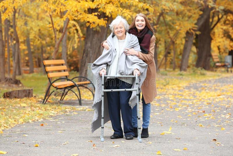 Ältere Frau mit gehendem Rahmen und junge Pflegekraft stockbild