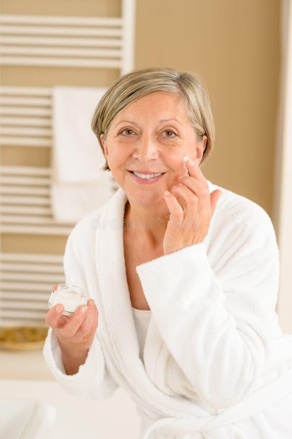 Ältere Frau mit Gesichtssahne im Badezimmer stockbild