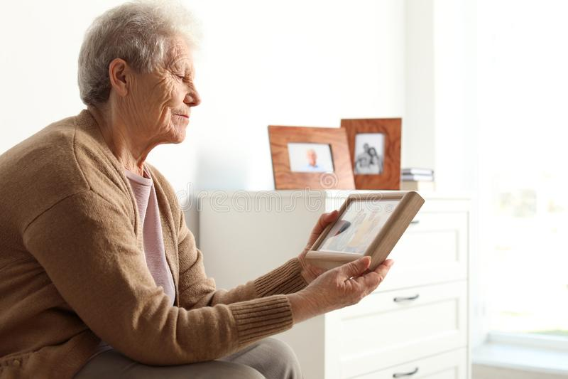 Ältere Frau mit gestaltetem Familienporträt stockfotos