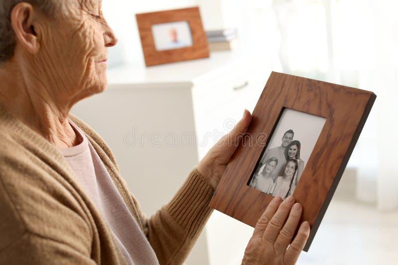Ältere Frau mit gestaltetem Familienporträt lizenzfreie stockfotos