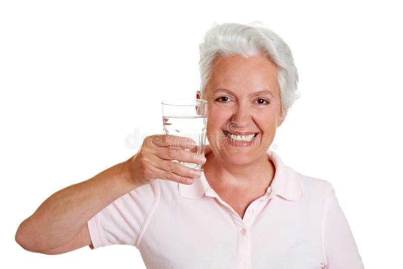 Ältere Frau mit Glas Wasser stockfoto