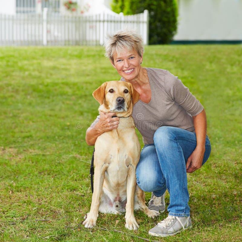 Ältere Frau mit Hund im Garten stockfotos