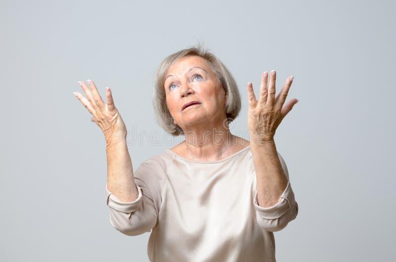 Ältere Frau mit ihren Händen bis zum Himmel stockfotos