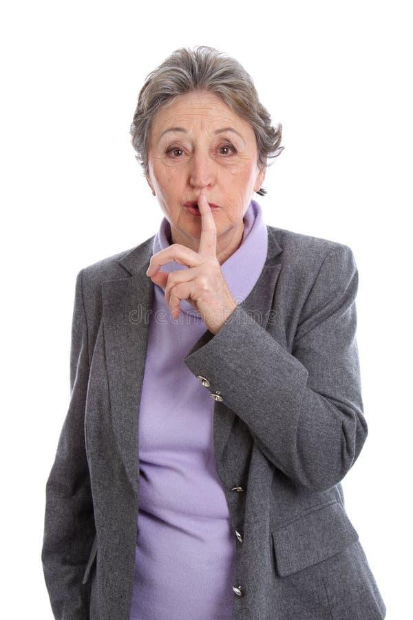 Ältere Frau mit ist ruhiges Zeichen - die ältere Frau, die auf Weiß lokalisiert wird stockfotografie