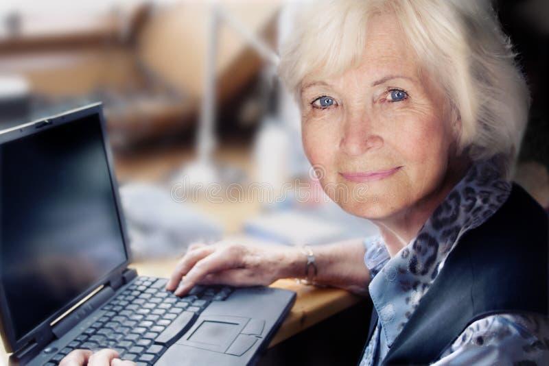 Ältere Frau mit Laptop lizenzfreies stockbild