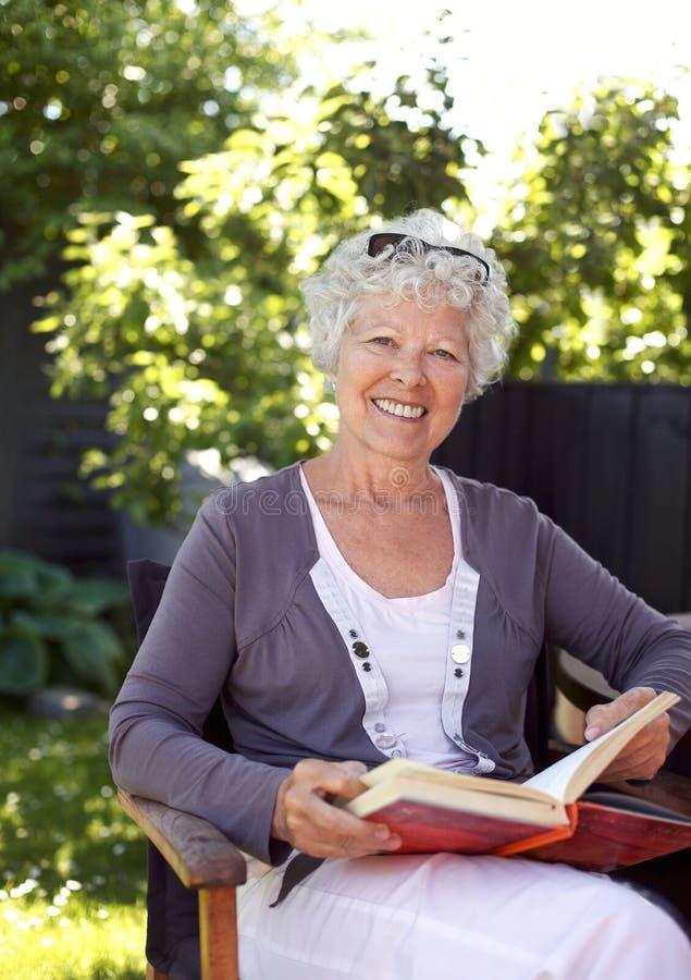 Ältere Frau mit Roman im Garten lizenzfreie stockfotografie