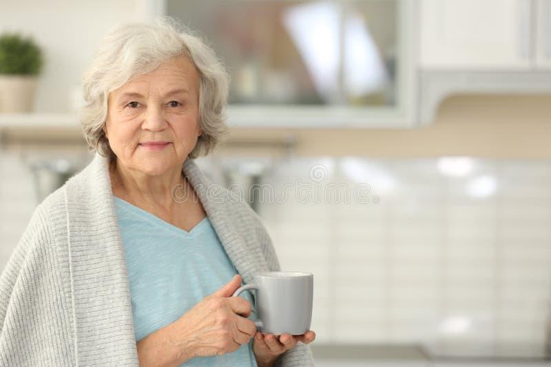 Ältere Frau mit Tasse Tee in der Küche stockbild