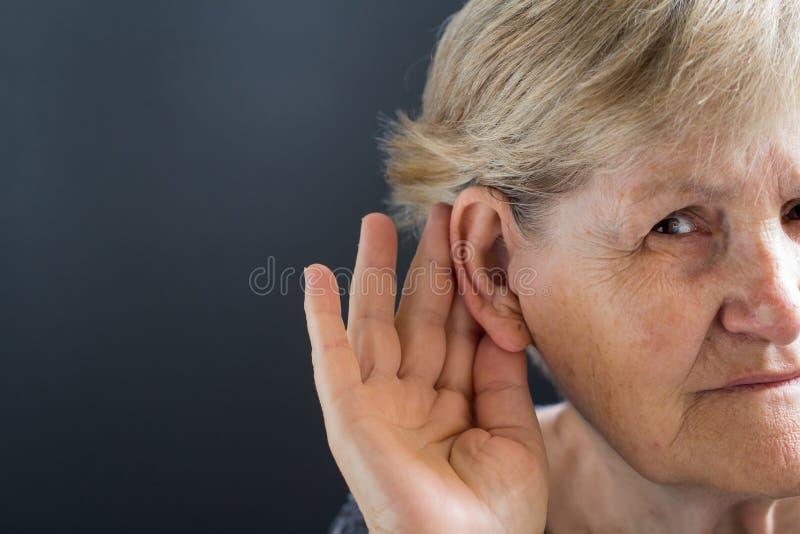 Ältere Frau mit Verlust der Hörfähigkeit auf grauem Hintergrund Altersgebunden stockfotos