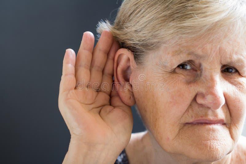 Ältere Frau mit Verlust der Hörfähigkeit auf grauem Hintergrund Altersgebunden lizenzfreie stockfotos
