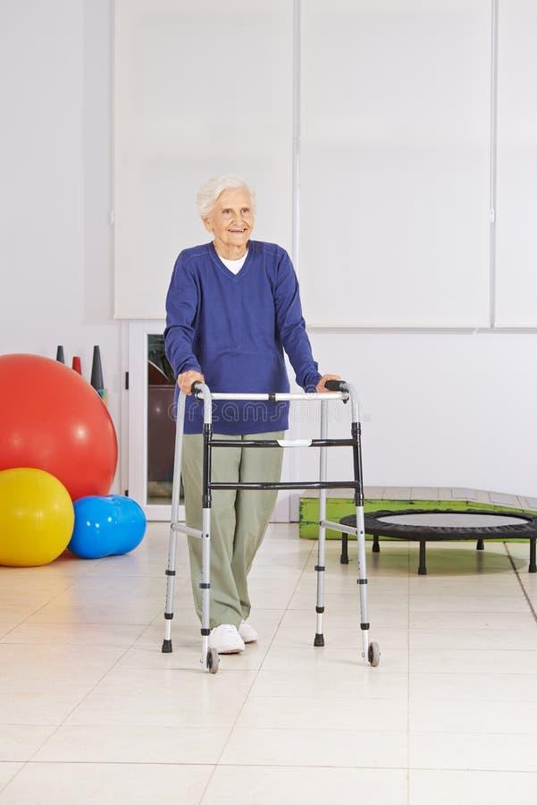Ältere Frau mit Wanderer in der Physiotherapie stockfoto
