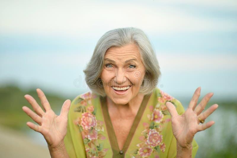 Ältere Frau nahe See stockfotografie