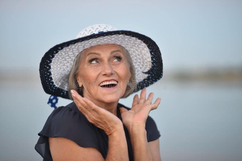 Ältere Frau nahe See stockbilder