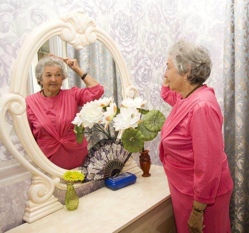 Ältere Frau nahe Spiegel stockfoto