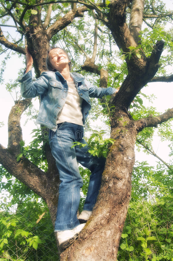 Ältere Frau oben auf einem Baum