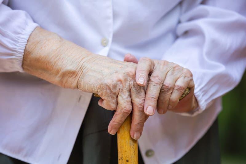Ältere Frau ` s Hände, die Spazierstock halten stockfotografie