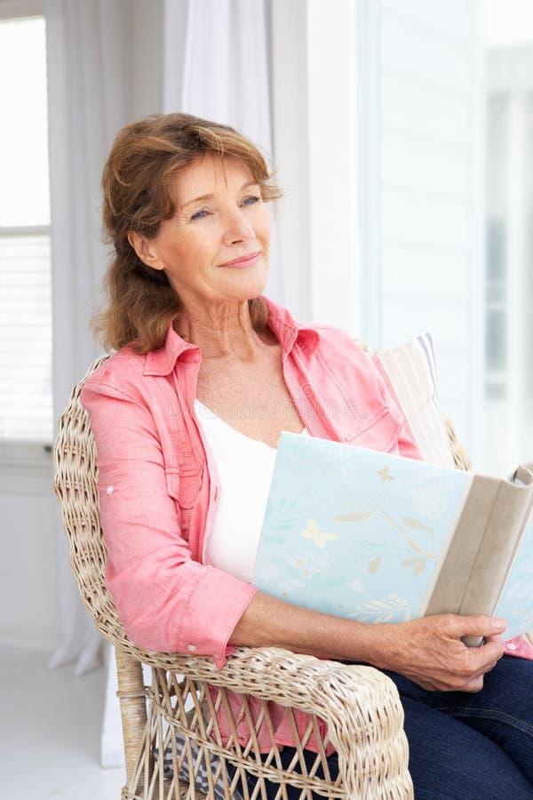 Ältere Frau saß mit Fotoalbum stockfotos