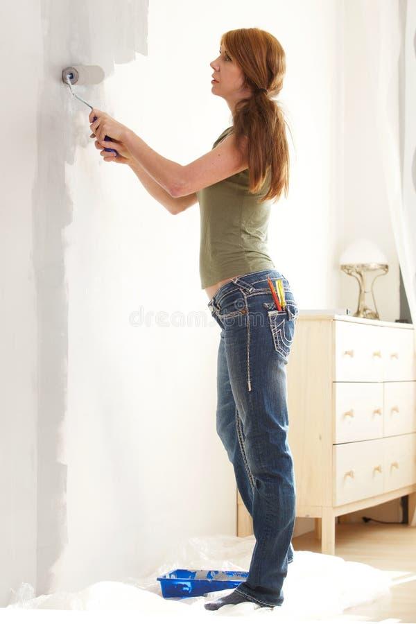 Ältere Frau selbst, welche die Wände malt stockbilder