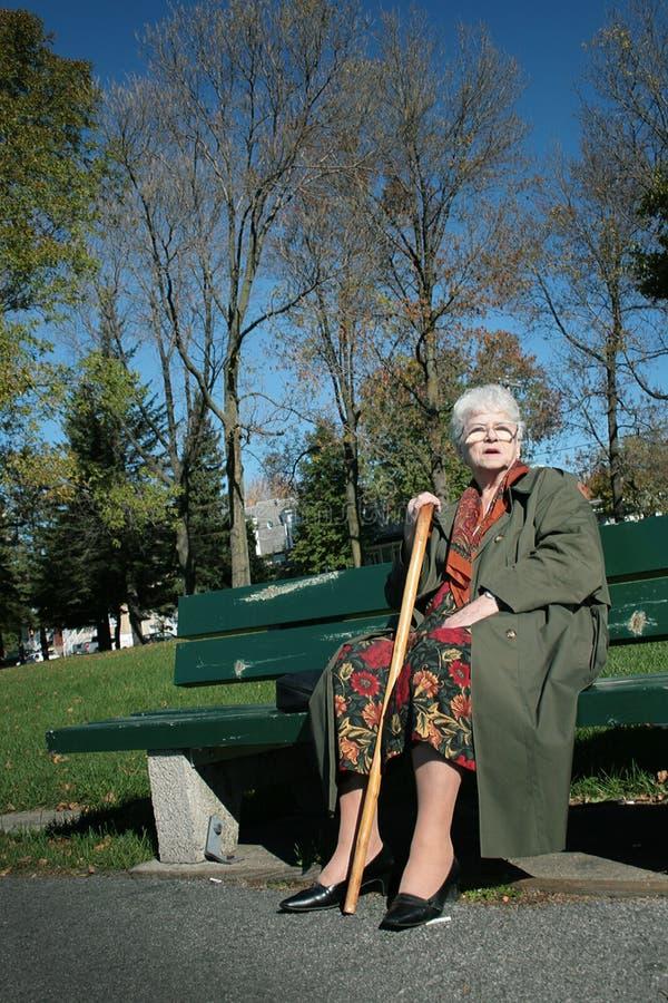 Ältere Frau sitzen auf einer Bank stockfotos