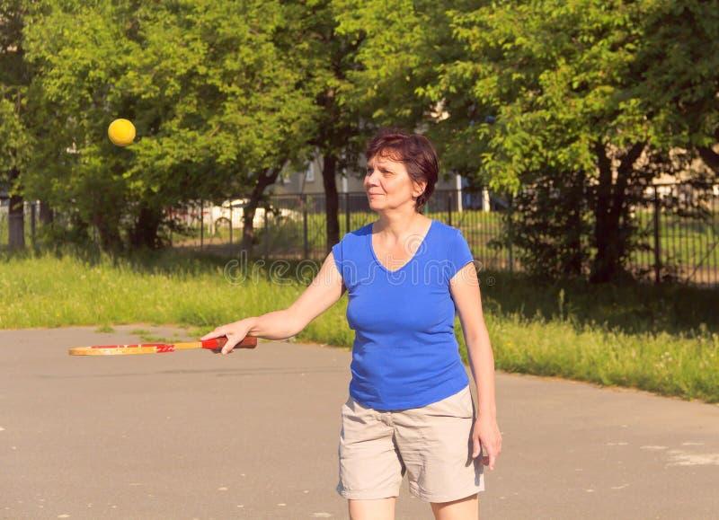 Ältere Frau spielt mit einem Tennisball und einem Schläger lizenzfreie stockfotos