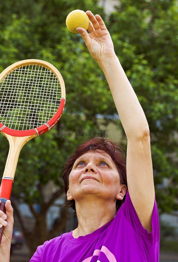 Ältere Frau spielt mit einem Tennisball und einem Schläger Auf dem Spielplatz im Sommer stockfotografie