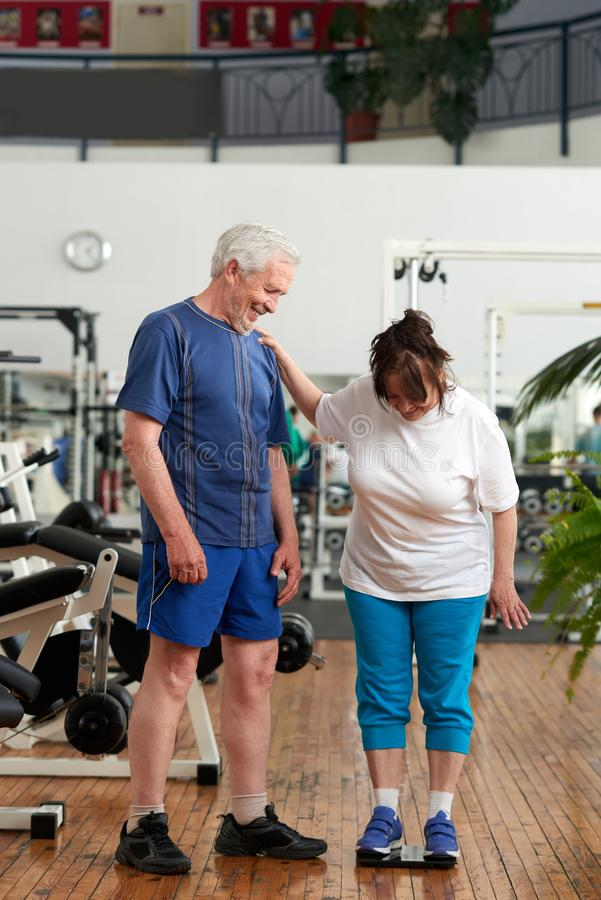 Ältere Frau steht auf Gewichtsskala an der Turnhalle stockfoto