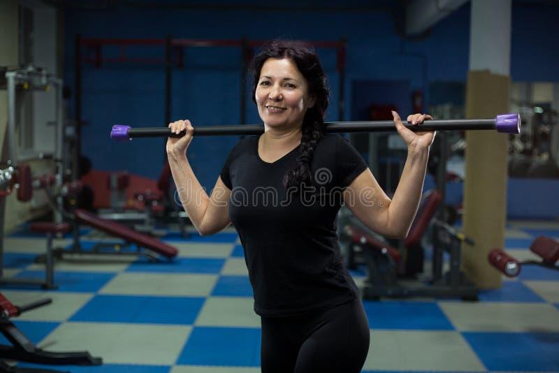 ?ltere Frau steht in der Turnhalle mit einer K?rperstange auf ihren Schultern Nahaufnahme Kopieren Sie Platz stockbilder