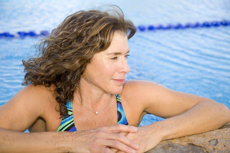 Ältere Frau am Swimmingpool stockfotos