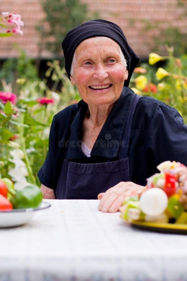 Ältere Frau am Tisch lizenzfreie stockfotos