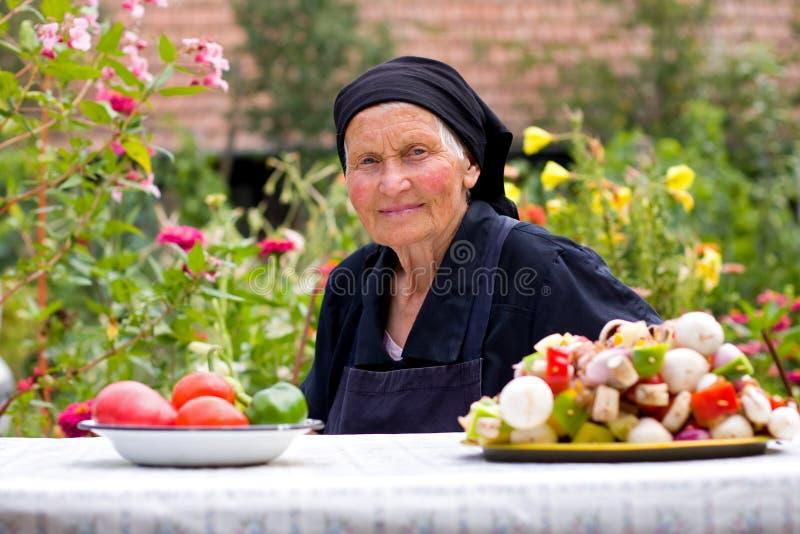 Ältere Frau am Tisch stockfotografie