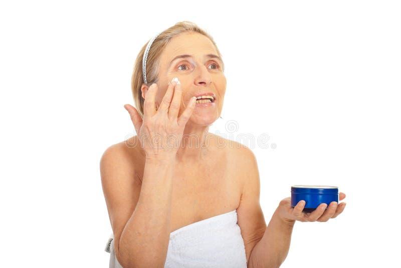 Ältere Frau tragen Hautsorgfaltsahne auf lizenzfreie stockfotografie
