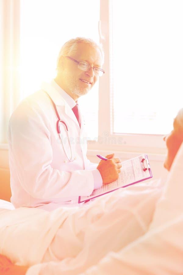 Ältere Frau und Doktor mit Klemmbrett am Krankenhaus stockbild