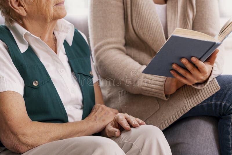 Ältere Frau und hilfreicher Freiwilliger am Pflegeheimablesenbuch zusammen lizenzfreie stockfotografie