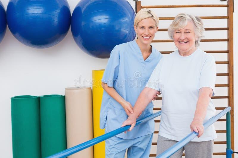 Ältere Frau und Therapeut, die an der Kamera lächelt lizenzfreie stockbilder