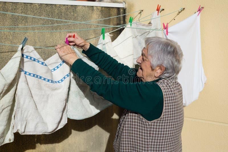 Ältere Frau, welche heraus die Reinigung hängt stockbilder