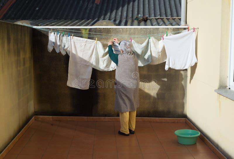 Ältere Frau, welche heraus die Reinigung hängt lizenzfreie stockbilder