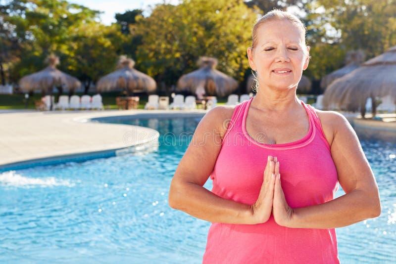 Ältere Frau am Wellnesspool faltet ihre Hände während der Yogameditation stockfoto