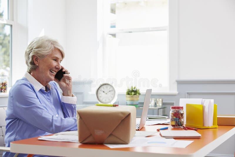 Ältere Frau zu Hause, die Kurier Collection For Package bucht lizenzfreies stockfoto